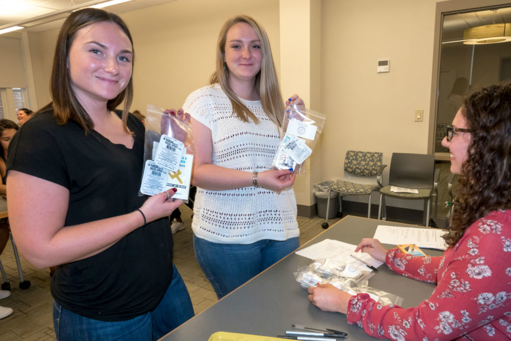 Sage Nursing students hold kits containing naloxone and caregiver protection tools.