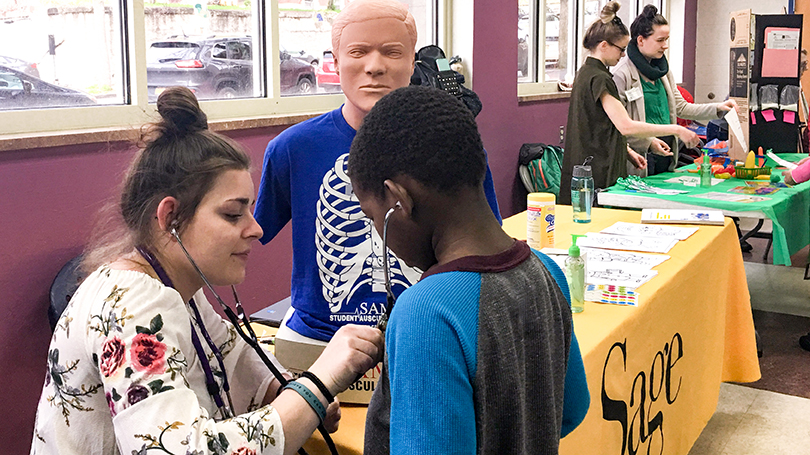 A Russell Sage College Nursing student demonstrates a stethoscope during an activity fair at the Boys & Girls Clubs of the Capital Area in Troy.