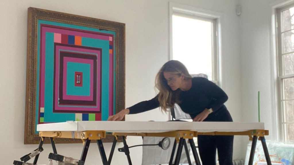 """Artist Michelle Bowen working in her studio; """"Real and Fake Inside News"""" hangs in the background."""